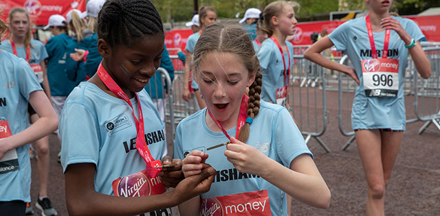 Two runners celebrate completing the Virgin Money Giving Mini London Marathon